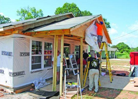 Volunteers raising two new houses near Millard Fuller's hometown